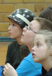Third graders (from left) Lucian MacGregor, AJ Blasnitz and Harley Smith listen intently to Bob Glenn.
