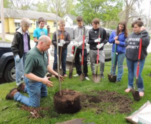 Brad Riphagen explains planting a tree to eighth graders while tree committee member Carole Fisher (left) waits to add water.