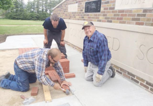 Keith Devilbiss (right) helping lay brick pavers at the school monument