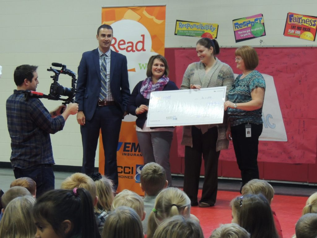 Jeff Less of EMC Insurance presents a check to (from left) Wendy Vander Linden, media specialist Jenny Fisher and media associate Karla Maston as a KCCI cameraman records the event.